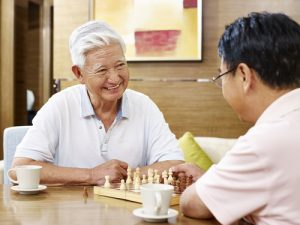 Two men discussing care for seniors over a game of chess